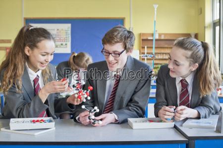 high school students assembling molecule model