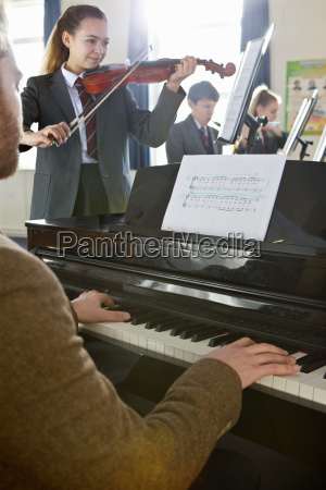middle school students and teacher playing