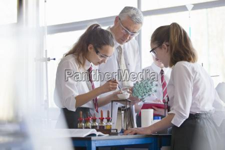 chemistry teacher helping high school students