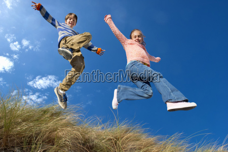 exuberant brother and sister jumping for