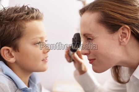 optician performing eye exam on boy