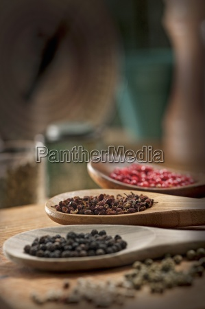 various types of peppercorns on wooden