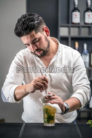 bartender preparing mojito cocktail