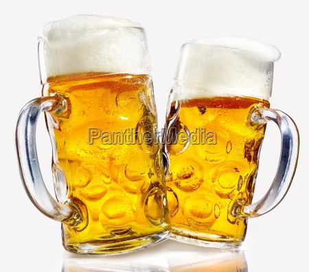 two glass beer mugs full of