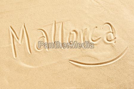 mallorca handwritten in golden beach sand