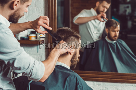 young handsome barber making haircut of