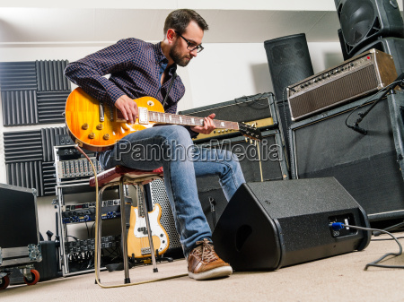 playing electric guitar in a studio
