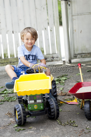 little boy on his toy tractor