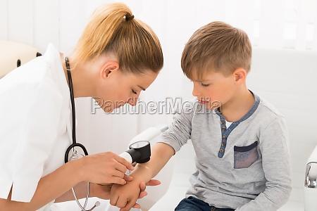 doctor examining skin of little boy