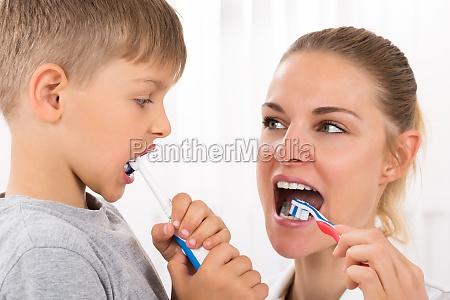 doctor and boy brushing teeth