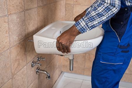 handyman fixing sink in bathroom
