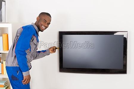 male technician repairing television