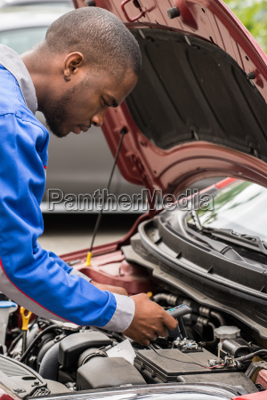 mechanic checking car battery with multimeter