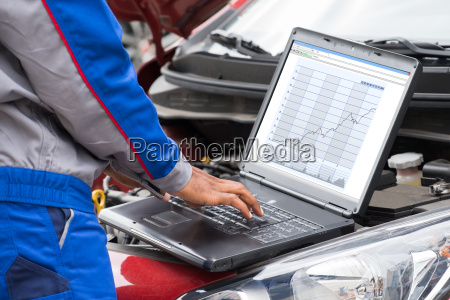 mechanic using laptop for examining car