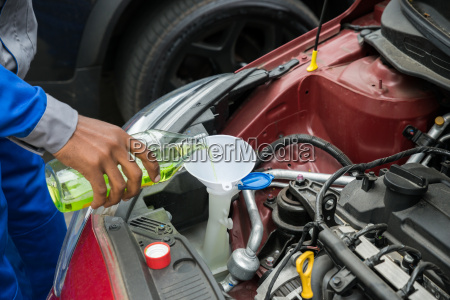 mechanic pouring oil into the car