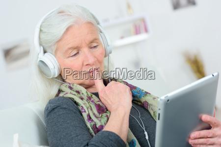senior lady listening to music through
