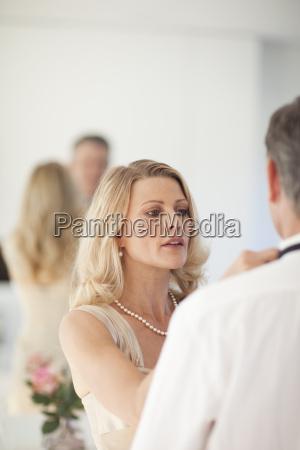 mature woman adjusting bow tie on