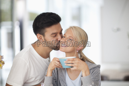 mid adult man kissing woman holding