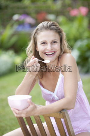 portrait of young woman eating outdoors