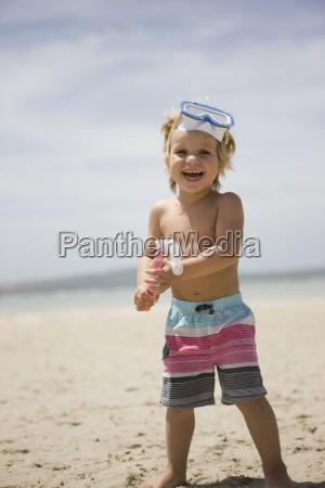 boy holding snorkel on beach portrait