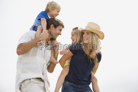 father and mother carrying children children
