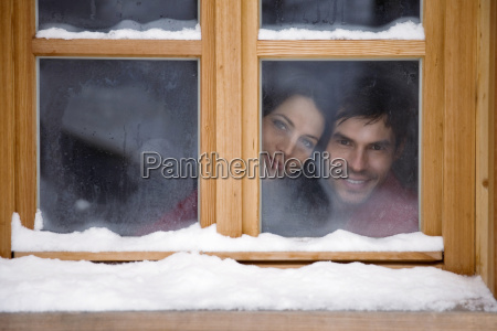 mid adult couple looking through window