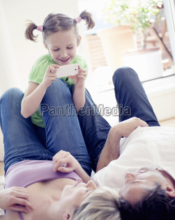 girl photographing mother and father on