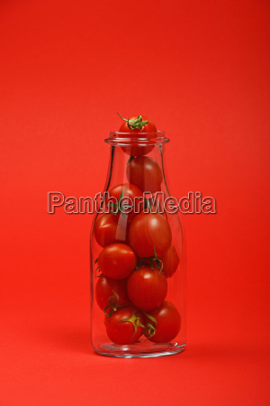 cherry tomatoes in glass bottle over