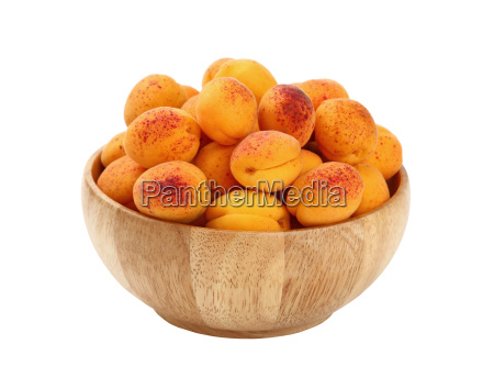 ripe fresh apricots in wooden bowl