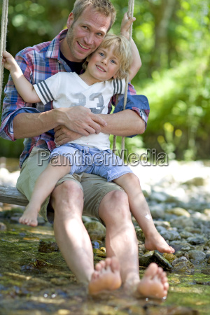 man and young boy on swing