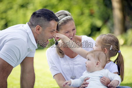 daughter pulling fathers nose in park