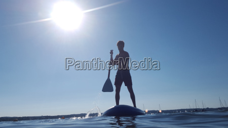 teenage boy paddle boarding on lake