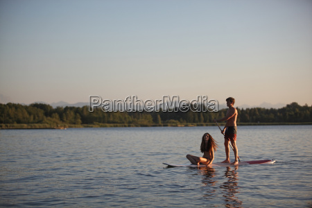 teenage couple on paddleboard on lake