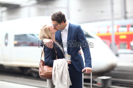 business couple kissing on train platform