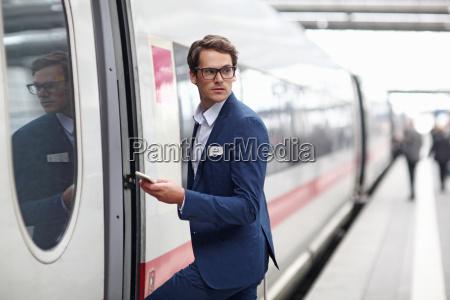 businessman getting on train on platform