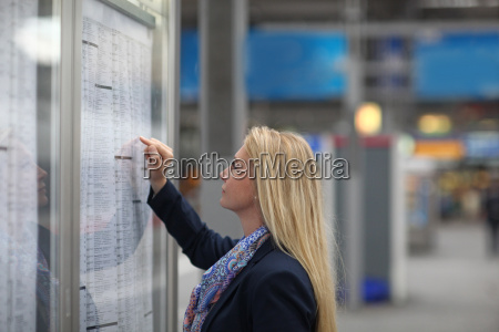 mid adult woman studying train timetable
