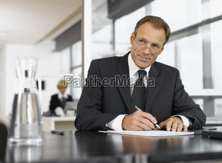 middle aged businessman writing at desk