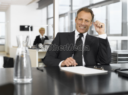 businessman smiling at desk with paperwork