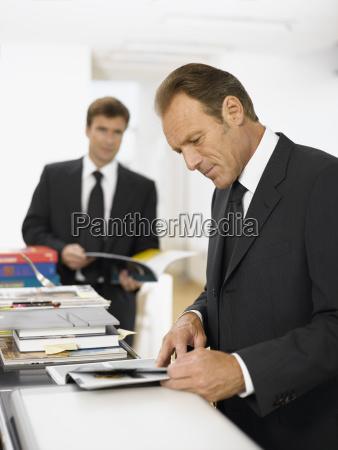 businessmen looking at paperwork in office