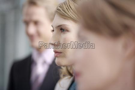businesswoman standing between co workers