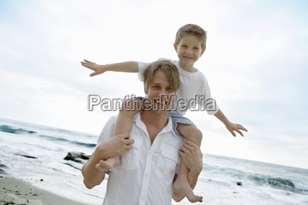 father carrying son on shoulders at