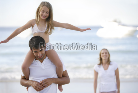 father holding daughter on shoulders while