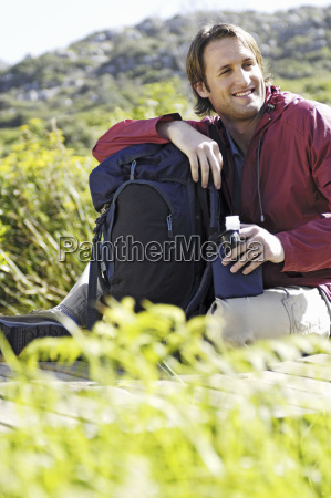 man, sitting, outdoors, with, backpack, and - 18096724