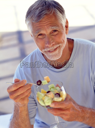 portrait, of, mature, man, eating, fruit - 18098112