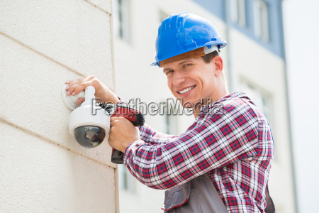 young male technician installing camera on