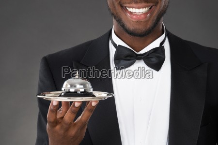 african waiter holding service bell