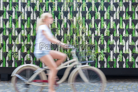 woman riding bycicle by green urban