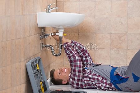 plumber lying on floor fixing sink