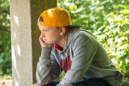 upset boy sitting in park