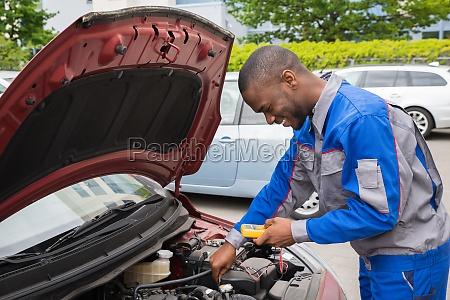 mechanic using multimeter to check car